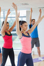 Sporty people doing power fitness exercise at yoga class in studio Royalty Free Stock Image