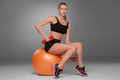 Sporty woman doing aerobic exercise with red dumbbells on a fitness ball on grey background Royalty Free Stock Photo