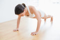 Sporty woman doing push ups in fitness studio full length of a young Stock Photography
