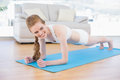 Sporty woman doing push ups in fitness studio smiling beautiful young on exercise mat Royalty Free Stock Images