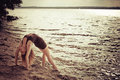 Sporty woman doing stretching exercise on the bank Royalty Free Stock Photography