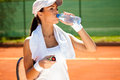 Sporty woman drinking water after tennis training Royalty Free Stock Images