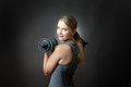 Sporty woman on grey background with dumbbells studio shot of a pretty young fitness model holding and looking back over her Royalty Free Stock Photos