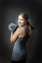 Sporty woman on grey background with dumbbells studio shot of a pretty young fitness model holding and looking back over her Royalty Free Stock Photography