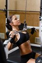 Sporty woman in the gym sports young doing exercises on lat machine Stock Photography