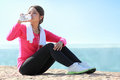 Sporty woman have a break portrait of asian fitness drinking bottle of water while having Royalty Free Stock Image