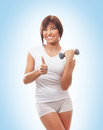 A sporty woman holding a dumbbell girl with dumbbells over blue background Stock Photo