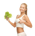 Sporty woman with lettuce showing abs picture of beautiful Royalty Free Stock Photos
