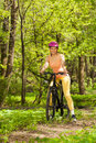 Sporty woman with mountain bike on woodland trail Royalty Free Stock Photo