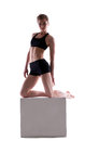 Sporty woman posing with cube looking at camera isolated on white Royalty Free Stock Photography