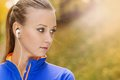 Sporty woman runner listens to music in nature and active is listening before outdoor exercise Stock Photo