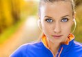 Sporty woman runner listens to music in nature and active is listening before outdoor exercise Royalty Free Stock Images