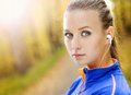 Sporty woman runner listens to music in nature and active is listening before outdoor exercise Royalty Free Stock Photos
