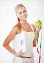 Sporty woman with scale, apple and measuring tape Royalty Free Stock Photo