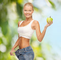 Sporty woman showing big pants diet and sport concept picture of and apple Stock Image