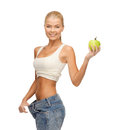 Sporty woman showing big pants picture of and apple Royalty Free Stock Photos