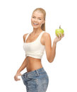 Sporty woman showing big pants picture of and apple Royalty Free Stock Photography
