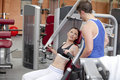 Sporty woman sitting on a shoulder press talking Royalty Free Stock Photography