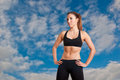 Sporty woman standing up with arms resting at her waist with a cloudy sky behind her Royalty Free Stock Photo