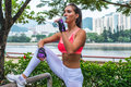 Sporty young female athlete taking a break after exercising or running, standing and drinking water from bottle in park