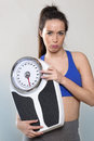 Sporty young lady with scales and poney tail sports concept frowning athletic woman wearing sportswear holding big weighting scale Royalty Free Stock Photos