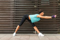 Sporty young woman doing wide-legged forward bend exercise holding her arms straight on the city street. Royalty Free Stock Photo