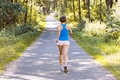 Sporty young woman runner running on the road in forest Royalty Free Stock Photography