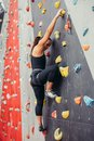 Sporty young woman training in a colorful climbing gym. Royalty Free Stock Photo