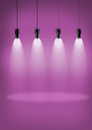 Spotlights pink wall four black hanging from a ceiling shining down on the floor with a purple in the background Stock Photo