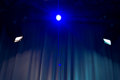 Spotlights shining on an empty venue with a white curtained backdrop with a central colourful blue light flanked by side lights Royalty Free Stock Photo