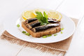 Sprats sandwiches on white plate on wooden table Royalty Free Stock Photo