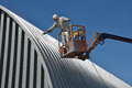 Spraying the roof tradesman spray painting of an industrial building Royalty Free Stock Images
