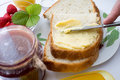 Spreading bread with butter for breakfast Stock Image