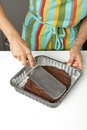 Spreading out the chocolate paste in the mould Royalty Free Stock Photos