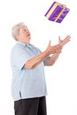 Sprightly senior catches or throws  gift Royalty Free Stock Images