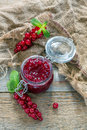Sprigs of red currants and a jar of homemade jam. Royalty Free Stock Photo