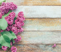 Spring background with a bouquet of lilac flowers on wooden plank