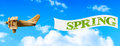 Spring banner vintage wooden toy plane flying in blue sky pulling a to bring in Stock Image