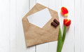 Spring bouquet of red tulips and a card in an envelope Royalty Free Stock Photo