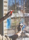 Spring cleaning - cleaning windows. Women`s hands wash the window, cleaning