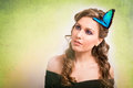 Spring concept of a blonde woman with a blue butterfly in her ha Royalty Free Stock Photo