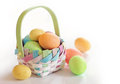 Spring easter eggs in a basket colorful on white background Royalty Free Stock Photography