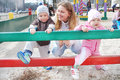 Spring family boy girl mom play in the playground sandbox Royalty Free Stock Photos