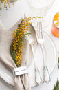 Spring festive dining table setting with yellow mimosa flowers candles napkins and vintage cutlery on a white wooden board Stock Images