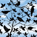 Spring floral seamless wallpaper with birds on branches over blue sky silhouette branch and leaf background pattern ornamental Royalty Free Stock Photo