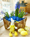Spring flowers in a small basket and easter rabbit Royalty Free Stock Photo