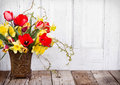 Spring flowers in a vase tulips and daffodils on white wooden background Stock Photos