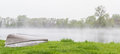 Spring fog over the lake early morning lingering with vivid green trees surrounding it and a small fishing boat Stock Photography