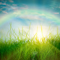 Spring green grass rainbow and and sun on blue sky background Royalty Free Stock Photo