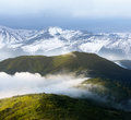 Spring landscape with snow covered mountains and fog Royalty Free Stock Photo